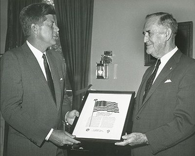"""Under God"" honored. Supreme Knight Luke E. Hart presents President John F. Kennedy, a fellow Knight of Columbus, with a framed copy of the Pledge of Allegiance. (Twitter)"
